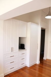kitchen with wooden floor and white cupboard