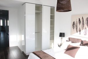 wardrobes with door open and a bed